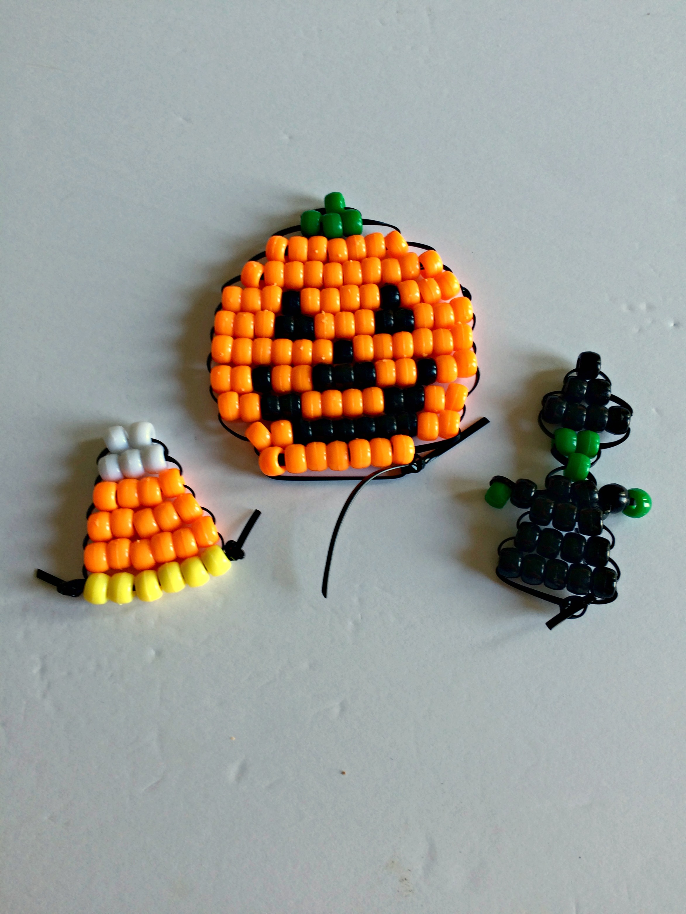 Halloween pony bead beadie buddies - a jack-o'-lantern, a candy corn, and a witch.