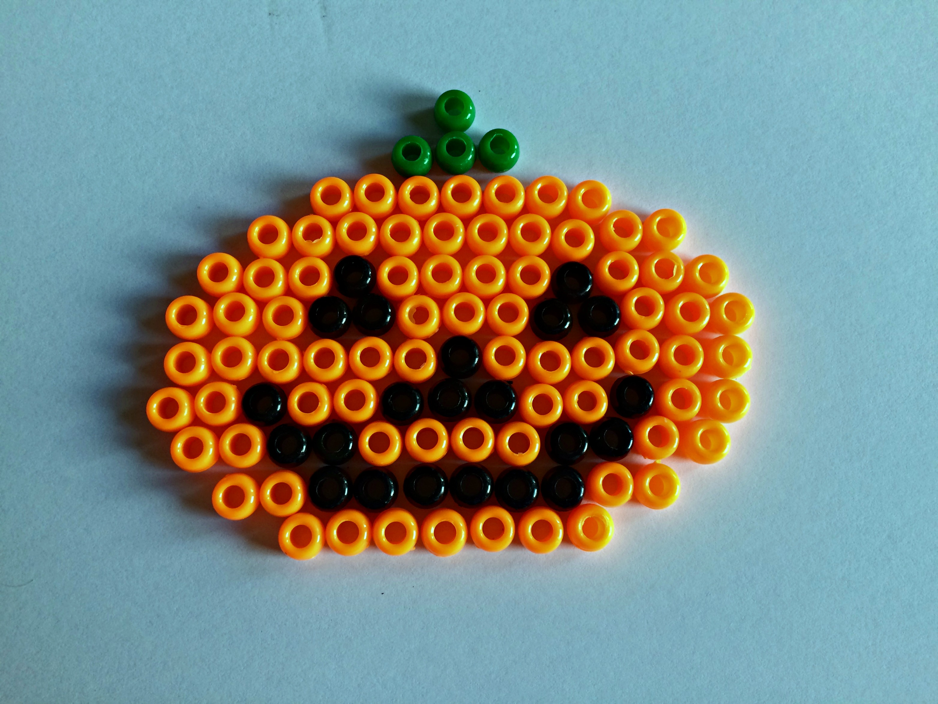 Pony beads laid out for a jack-o'-lantern beadie buddie design.