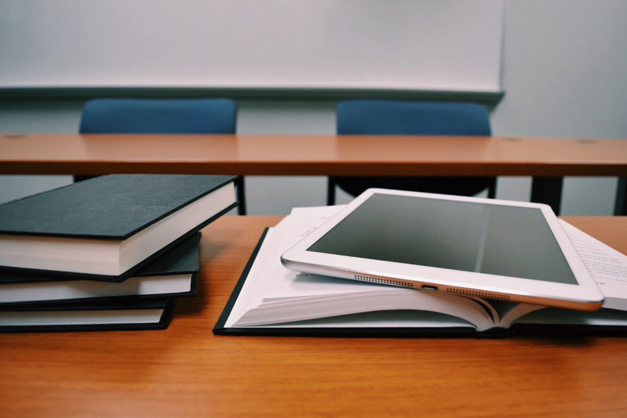 Books and a tablet in a university seminar room - a tablet can be very effective for your university note-taking.