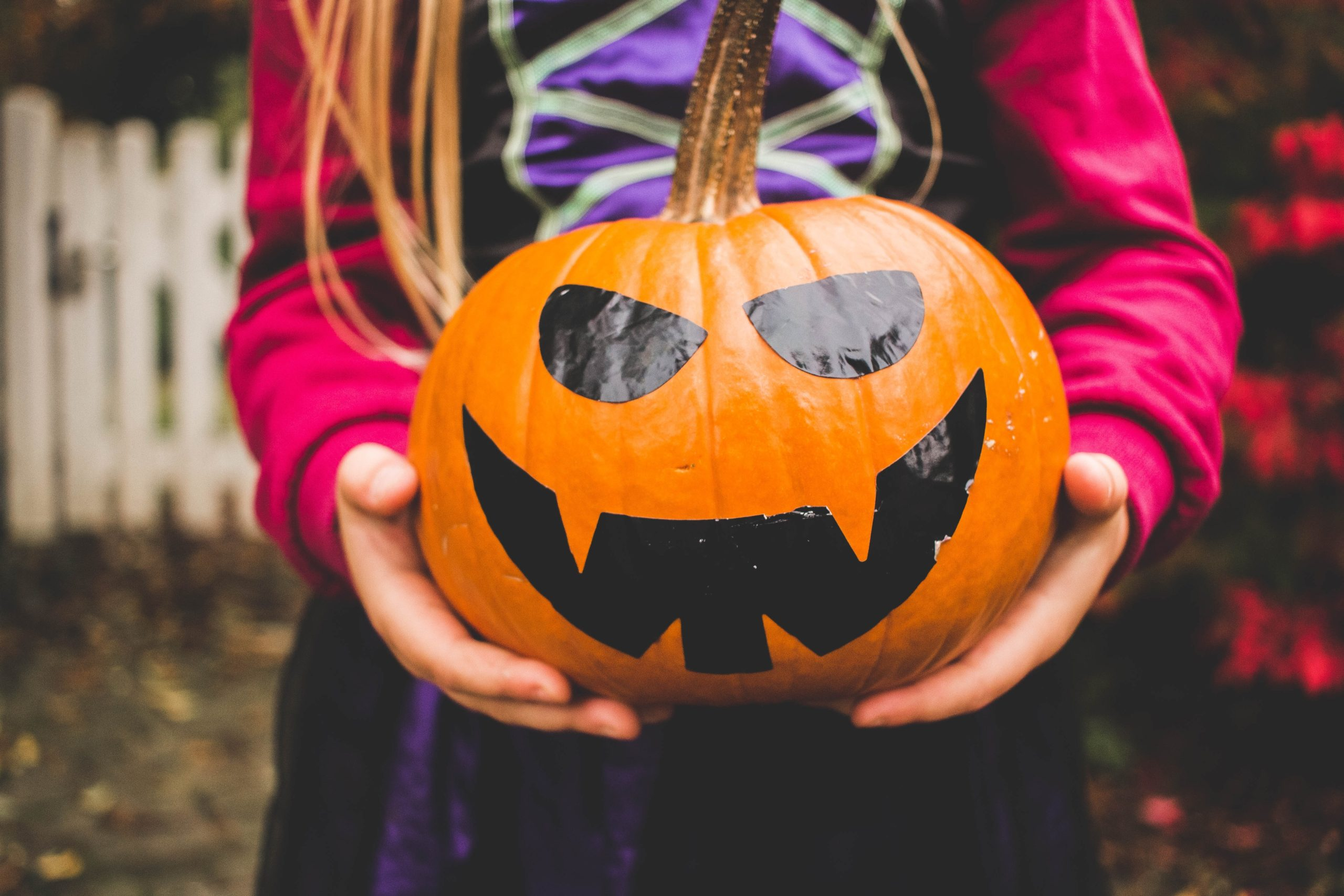 An image of a child in a Halloween costume holding a jack-o-lantern.